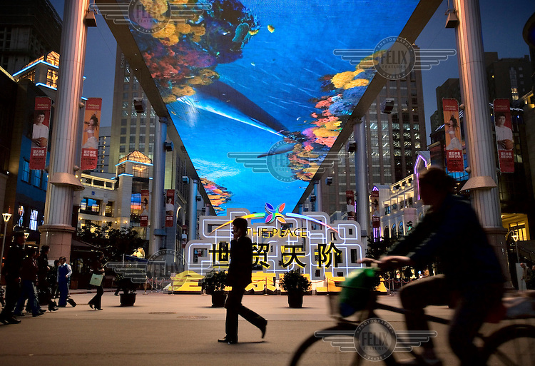"""People walk and cycle past """"The Place"""", a new open-air shopping mall with the biggest LCD television screen in Asia as its roof."""