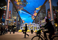 "People walk and cycle past ""The Place"", a new open-air shopping mall with the biggest LCD television screen in Asia as its roof."