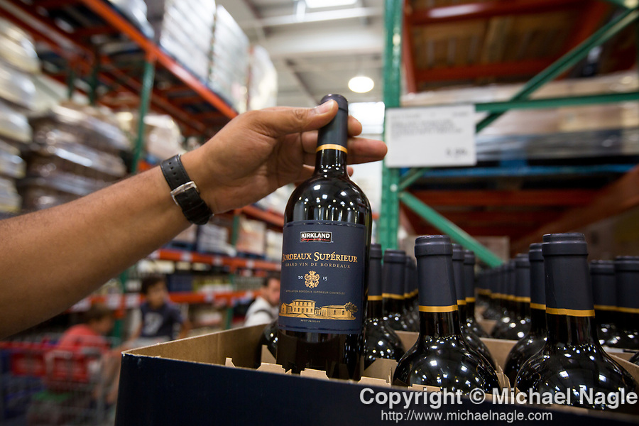 A Costco Wholesale Corp. member holds up a store brand Bordeaux at a newly opened Costco warehouse in Villebon-Sur-Yvette, France, on Saturday, July 7, 2018. The 150,000-square foot warehouse, which opened last month just outside of Paris, is Costco's first store in France. Costco plans to open 15 more warehouses in France by 2025. Photograph by Michael Nagle