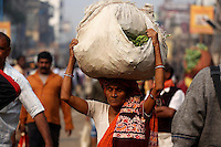 A woman carries bundle of vegetables on her head in the Kolay market in Kolkata.<br />