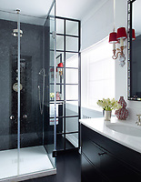 In the stylish guest bathroom, the vanity, topped in Thassos marble, and shower enclosure are custom made, and the fittings are by Lefroy Brooks.