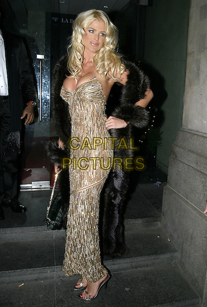 VICTORIA SILVSTEDT.At La Dolce Vita Ball in association with UNICEF,.Old Billingsgate, London, December 13th 2004..full length gold dress sequins beads beaded sequined black fur trimmed coat cleavage.Ref: AH.www.capitalpictures.com.sales@capitalpictures.com.©Capital Pictures.