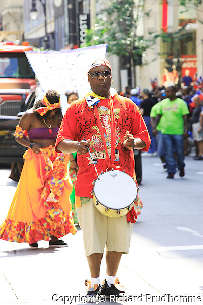 A mon playing a small drum walks in the Carifiesta parade in downtown Montreal