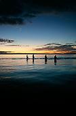Trout fishermen fishing the Waitahunui river mouth at sunset, Lake Taupo, Waikato, New Zealand