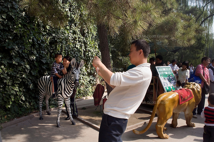 Tourists take pictures of children sitting on animal statues at the Beijing Zoo in Beijing, China.