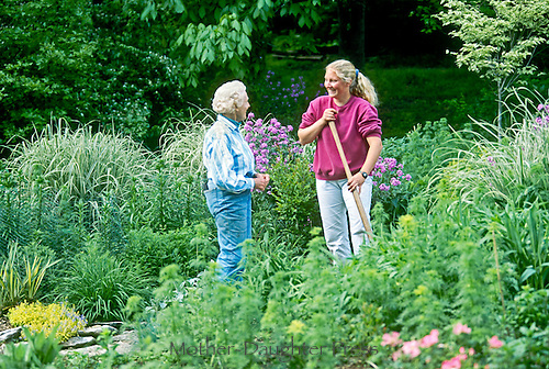 Mature woman and young woman confer in blooming garden on summer evening about gardening