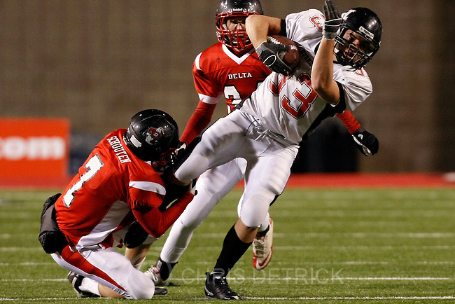 Chris Detrick  |  The Salt Lake Tribune .Hurricane's Jarom Healey #33 is tackled by Delta's Braden Schouten #7 and Kyle Church #34 during the first half of the 3A Semi-final game at Rice-Eccles Stadium Thursday November 11, 2010.