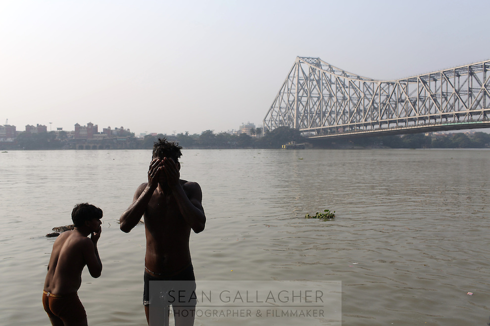 Two men wash in the Ganges River near near the Howrah bridge in Kolkata. Upon entering the city, the river is saturated with a mix of domestic and industrial waste that has accumulated as it has passed through numerous states in northern India, making it one of the most polluted rivers in the world. India. November, 2013