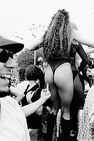 Switzerland. Zürich. A sexy woman, wearing a tight underwear, sexy stockings, high-heeled boots, dances during the Street Parade which is a yearly techno event in Zurich.  A young man shows up his middle finger ( fuck off) to the woman's bottom. © 1995 Didier Ruef