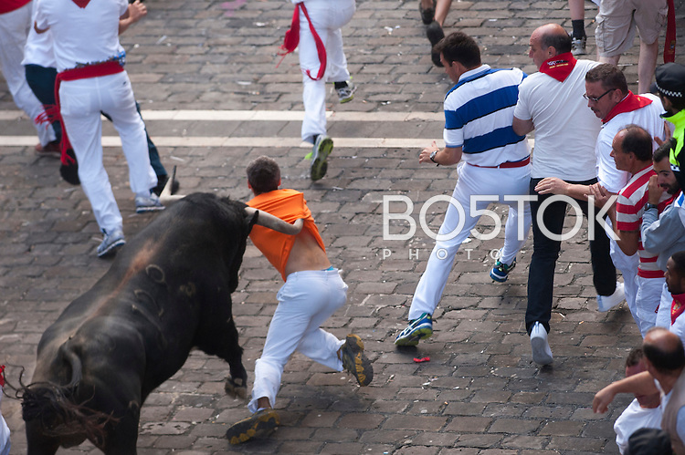 A runner gets pushed by a bull while running ahead of Victorino del Rio's fighting bulls during the San Fermin Festival´s running of the bulls. Iruñea-Pamplona (Basque Country) July 9, 2015. Every year, tens of thousands of people pack Pamplona's streets for a drunken kick-off to one os world's best-known fiesta: the nine-day San Fermin bull-running festival. (Gari Garaialde / Bostok Photo)