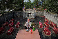 A former soldier Do Duc Diu prays at the cemetery where twelve of his children are buried after showing it to reporters near his house in Quang Binh Province in central Vietnam April 11, 2015. Twelve of his fifteen children already died of illnesses family and doctors link to father's exposure to the Agent Orange. Do Duc Diu served as a North Vietnamese soldier in early 70s in the areas already heavily contaminated by the Agent Orange but only found out about its dangers before his last child was born in 1994. He said that if he had known about the possible effects of the Agent Orange he would not have children. Before he found out about the Agent Orange issue, Do Duc Diu and his wife visited many spiritual leaders and prayed at different shrines linking sickens of their children to the ill fated destiny.  REUTERS/Damir Sagolj