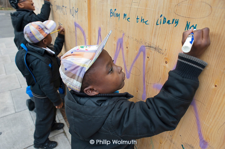 Local residents write messages of protest on boards sealing-up Preston Road Library, one of six libraries closed by Brent Council.