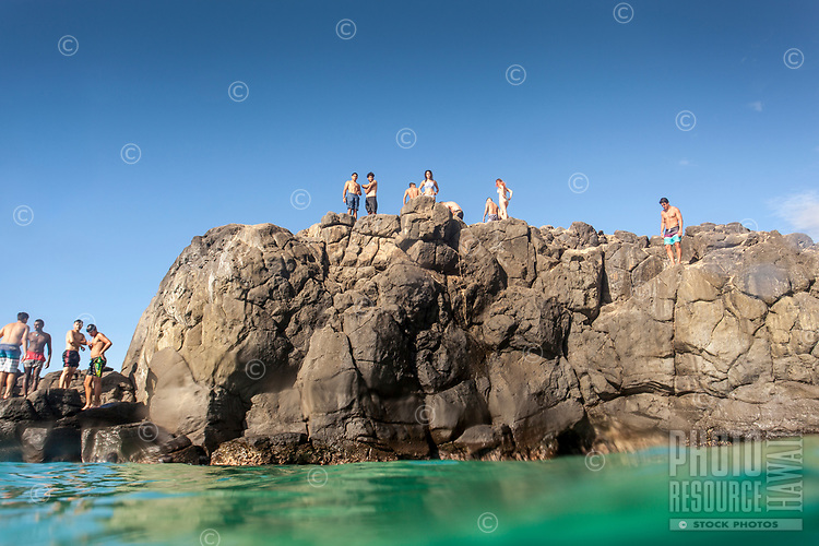 Beachgoers atop the famous (and dangerous) Jump Rock look out at Waimea Bay, O'ahu.