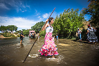 "A young girl recently baptized in the river, walk crossing over ""Vado del Quema"" as the cart of their brotherhood starts it."