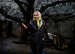 Avdiivka, eastern Ukraine, Nov. 2017.<br /> <br /> Valentina Fedorovna, 83, in her backyard, on the outskirts of Avdiivka.<br /> <br /> The house is on the frontline and has been badly damaged by heavy artillery shelling from pro-Russian separatists. <br /> <br /> A shell hit the front of her house on 23/5/17, smashing all the windows in the front, and spraying shrapnel into the rooms, but the house had already suffered damage from previous shelling and sniper fire.<br /> <br /> The sounds of explosions and gunfire can be heard every day, but she tries to carry on as normal, while receiving and giving support to the few elderly neighbours she has left.<br /> <br /> She has lived in the area all her life and moved to this house in the 1960&rsquo;s when she got married. <br /> <br /> Her children are constantly asking her to move in with them but she vows never to leave - <br /> &lsquo;I have been building my house for many years, how can I leave it alone&rsquo;.