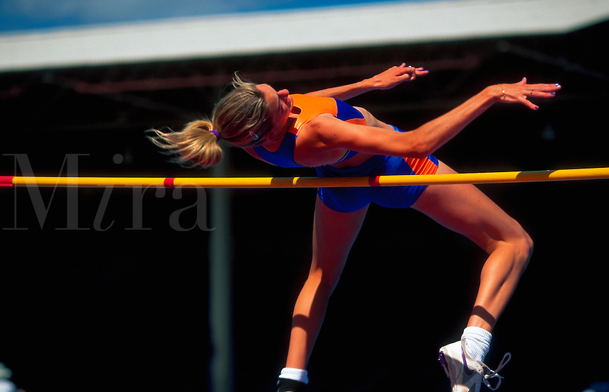 A female high jumper athlete personifies achievement of personal best.