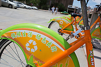 Docked bikeshare bicycles stand on a sidealk in Xian, China.