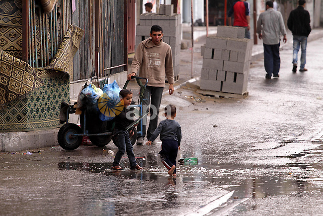 Palestinian children walk in a flooded street on an alley on a raining day at al-Shati refugee camp, the third largest in the Palestinian Territories, in Gaza City on October 30, 2013. Photo by Mohammed Asad