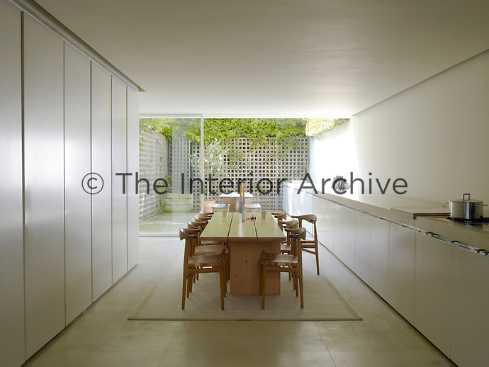 The limestone work surface and units run seamlessly the length of the kitchen and courtyard garden through the glass wall so that the two seem really to be one room