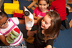 Education prechool 3 year olds group of three girls playing with puppets and laughing