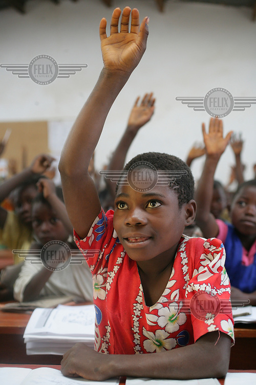 A portrait of a young child raising his arm to answer a question in class. Primary education is free of charge in Malawi. However, although many children start school, around 60% drop out before completing their primary schooling.