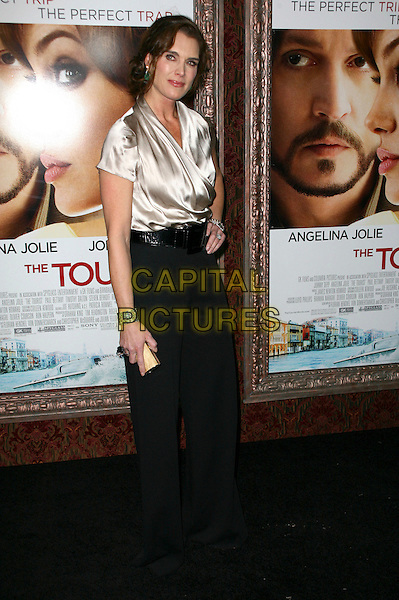 BROOKE SHIELDS.World premiere of 'The Tourist' at Ziegfeld Theatre in New York City, NY, USA, 6th December 2010..full length beige silk satin top blouse black trousers belt high waisted hand on hip clutch bag gold .CAP/ADM/PZ.©Paul Zimmerman/AdMedia/Capital Pictures.
