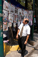 Man looking at Spanish language newspapers and magazines at a newstand in Mexico City