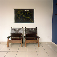 An artwork of a map of the world hangs above two wood and leather chairs.