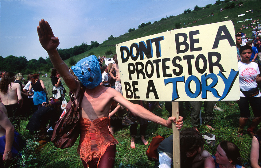 Masked protester holding placard with &quot;Don't be a protester be a Tory&quot; and making a Hitler salute. Road Protest actions at Twyford Down, near the Donga pathways, outside Winchester, against the M3 road extension. 1992-94<br />
