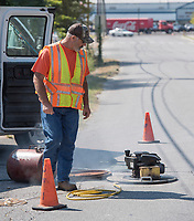 NWA Democrat-Gazette/J.T. WAMPLER Gary Perryman of Lowell monitors smoke pouring into pipes through a manhole Monday Sept. 11, 2017 during a smoke test in Springdale. From 8 a.m. to 5 p.m., Sept. 11-22, the Springdale Water Utilities will be performing the tests in an area south of East Huntsville Avenue to East Meadow Avenue and between Hewitt Street and Arkansas State Highway 265. The work is being performed in an effort to reduce the inflow of rain water into the sanitary sewer system and to reduce the cost of wastewater treatment.