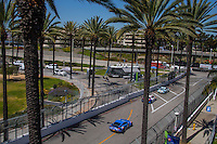 Cars race down a tree-lined street, Pirelli World challenge race, Long Beach Grand Prix, Long Beach, CA, April 2015.  (Photo by Brian Cleary/ www.bcpix.com )