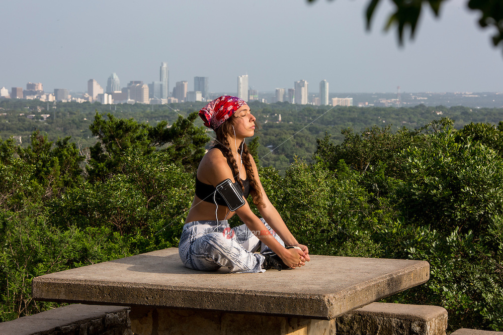 Portrait of a local Austin woman meditating yoga lotus pose on top of Mount Bonnell overlooking the Austin, Texas skyline.