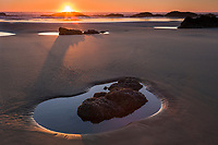 The sun sets over the ocean at low tide, leaving pools of water around the rocks. Oregon