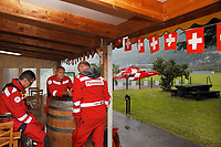 """Switzerland. Canton Ticino. Lodrino Air Base Airport (LSML). Rain and swiss flags. Intermediate landing for a Rega Augusta AW109 SP Grand """"Da Vinci"""" helicopter on a rescue mission. All Rega helicopters carry a crew of three: a pilot, an emergency physician, and a paramedic who is also trained to assist the pilot for radio communication, navigation, terrain/object avoidance, and winch operations. Left to right: Doctor Michele Musiari, pilot Corrado Sasselli and paramedic Paolo Menghetti. The name Rega was created by combining letters from the name """"Swiss Air Rescue Guard"""" as it was written in German (Schweizerische Rettungsflugwacht), French (Garde Aérienne Suisse de Sauvetage), and Italian (Guardia Aerea Svizzera di Soccorso). Rega is a private, non-profit air rescue service that provides emergency medical assistance in Switzerland. Rega mainly assists with mountain rescues, though it will also operate in other terrains when needed, most notably during life-threatening emergencies. As a non-profit foundation, Rega does not receive financial assistance from any government. People in distress can call for a helicopter rescue directly (phone number 1414). The AgustaWestland AW109 is a lightweight, twin-engine, helicopter built by the Italian manufacturer Leonardo S.p.A. (formerly AgustaWestland, Leonardo-Finmeccanica and Finmeccanica). Leonardo S.p.A is an Italian global high-tech company and one of the key players in aerospace. In close collaboration with the manufacturer, the Da Vinci has been specially designed to cater for Rega's particular requirements as regards carrying out operations in the mountains. It optimally fulfills the high demands made of it in terms of flying characteristics, emergency medical equipment and maintenance. Safety, performance and space have been increased, and maintenance and noise emissions reduced. 9.09.2017 © 2017 Didier Ruef"""
