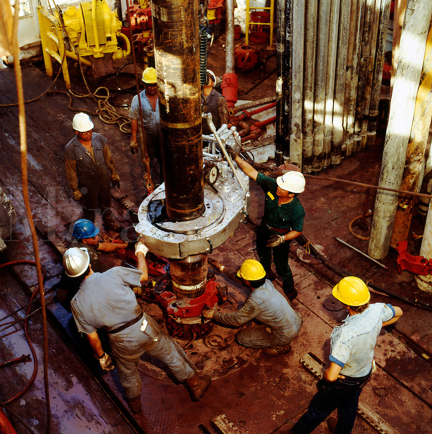 Casing crew working on oil rig drill floor.