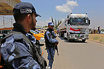 Palestinian security forces stand guard as Egyptian trucks carrying fuel arrive to Gaza's power plant in Nusseirat, in the central Gaza Strip after entering the southern Gaza Strip from Egypt through the Rafah border crossing on June 21, 2017. Egypt began to deliver a million litres of fuel to Gaza, a Palestinian official said, in an attempt to ease the Palestinian enclave's desperate electricity crisis. The fuel, trucked in through the Rafah border between Egypt and Gaza, will be routed to the territory's only power station -- closed since April due to fuel shortages. Photo by Ashraf Amra