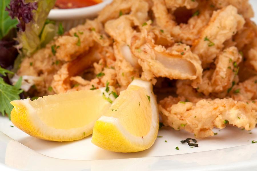 Macro of lemons and fried calamari, use of selective focus, plenty of copyspace.