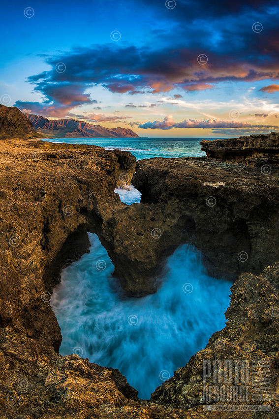 A heart-shaped rock formation along the coastline at sunset near Ka'ena Point, West O'ahu.