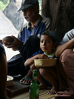 old man and child eating while villagers share rice, vegetable, meat and a light refreshing rice wine in village Bena, Ngada people, Flores, Indonesia