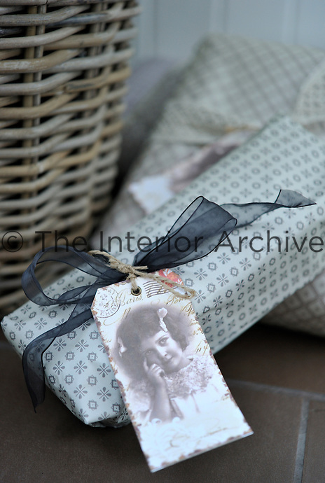 Detail of a vintage style label tied to one of the presents under the Christmas tree