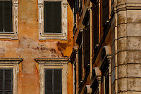 Detail of facades, Rome, Italy, pictured on December 11, 2010 in the afternoon. Elegant windows shaded by dark green shutters are set into the crumbling ochred walls of the old building in central Rome. Picture by Manuel Cohen