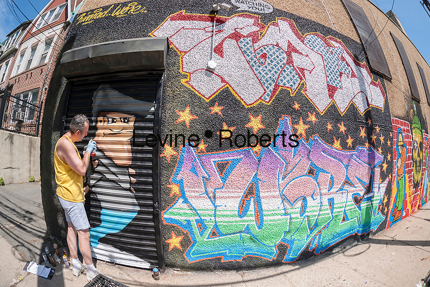 Street artist Zimad Wore at work on his mural at the Welling Court Mural Project in the Astoria neighborhood of Queens in New York on Saturday, June 13, 2015. The annual neighborhood event decorates walls in this industrial part of Astoria. The project is crowd-funded and emerging street artists work side by side with established stars.  (©Richard B. Levine)
