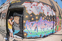 Street artist Zimad Wore at work on his mural at the Welling Court Mural Project in the Astoria neighborhood of Queens in New York on Saturday, June 13, 2015. The annual neighborhood event decorates walls in this industrial part of Astoria. The project is crowd-funded and emerging street artists work side by side with established stars.  (© Richard B. Levine)