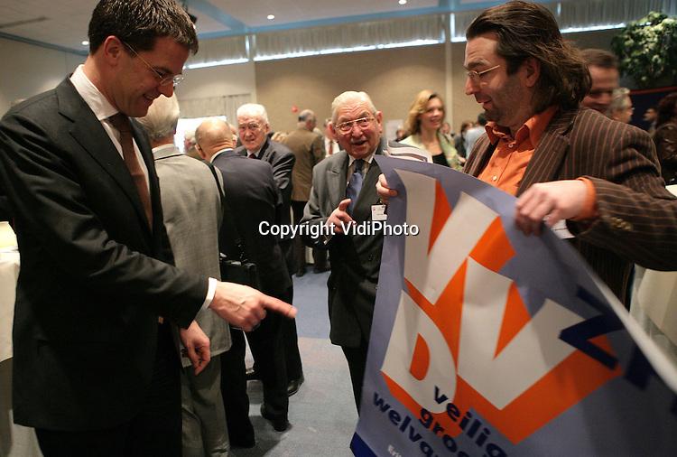 Foto: VidiPhoto..ARNHEM - De VVD maakt zich op voor de oppositie tegen het nieuwe centrumlinkse kabinet. Dat was de tendens zaterdag van de 121e algemene vergadering van de VVD, die werd gehouden in het hotel- en congrescentrum Papendal bij Arnhem.  Tevens werd het startschot gegeven voor de provinciale verkiezingen van maart. Foto: Mark Rutte bekijk een verkiezingsposter voor de Provinciale Statenverkiezingen.