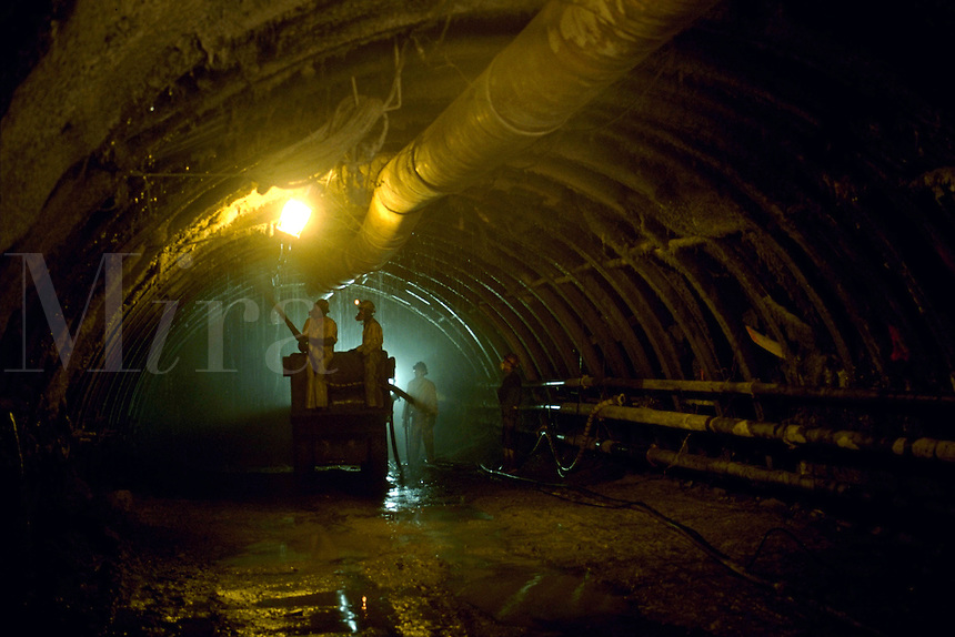To help reinforce the walls of a tunnel, workers spray shotcrete. The tunnel was being built for passenger train use. Tunnel workers.