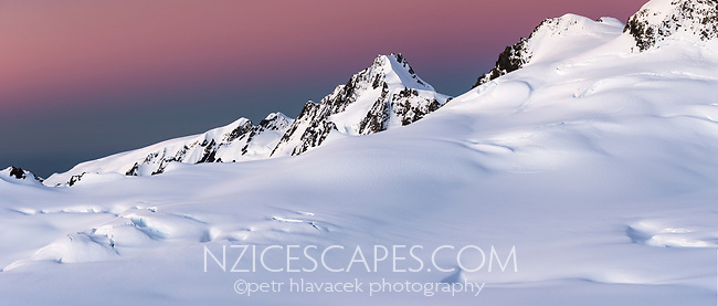 Dusk twilight over Bismarck Peaks and mountain ranges of Southern Alps with Explorer Glacier crevasses in upper parts of Fox Glacier NEVE, Westland Tai Poutini National Park, West Coast, UNESCO World Heritage Area, New Zealand, NZ