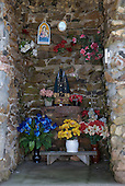 Fazenda Bauplatz, Brazil. Shrine to the Black Madonna with floral tributes.