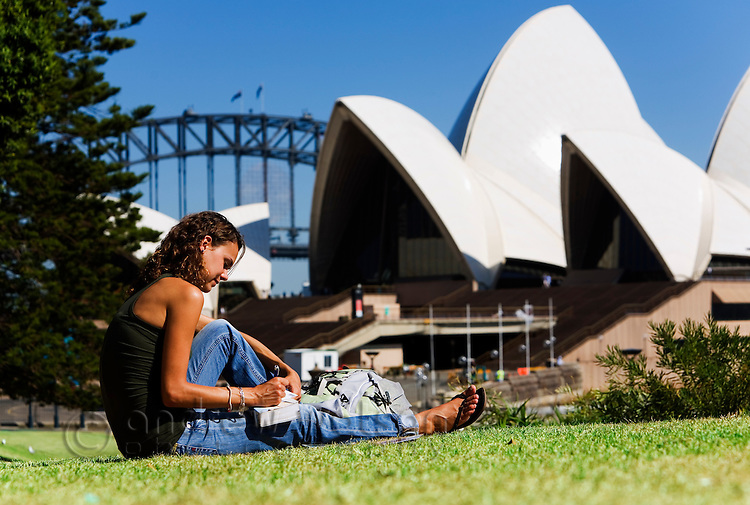 A woman writes postcards on the grass overlooking the Sydney Opera House.  Sydney, New South Wales, AUSTRALIA.