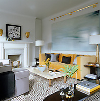 A painting by David Smith hangs over the fireplace and a large canvas covers the wall behind the sofa in the sophisticated living room