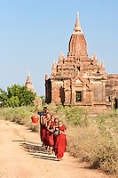 Myanmar, Burma. Bagan.  Young Novice Monks with Begging Bowls, Seeking Morning Food.